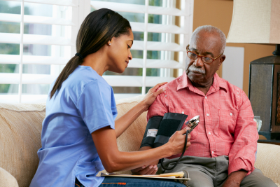 caregiver checking her patient blood pressure