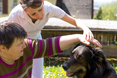 caregiver and her patient petting a dog